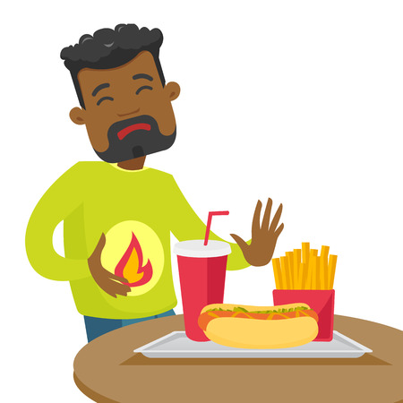 African-american man standing near table with fast food and having stomach ache from heartburn. Man suffering from a heartburn after fast food. Vector cartoon illustration isolated on white background Illusztráció