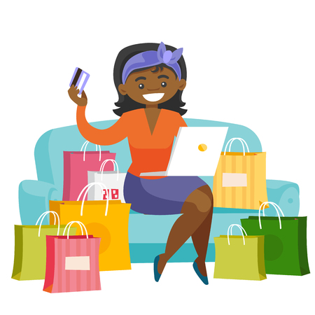 Young african woman sitting on the couch among shopping bags with laptop computer and credit card.