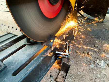 Professional mechanic is cutting steel metal with rotating diamond blade cutter. sparks while cutting steel. Selective Focus