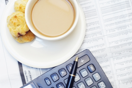 a cup of coffee and calculator on newspaper photo