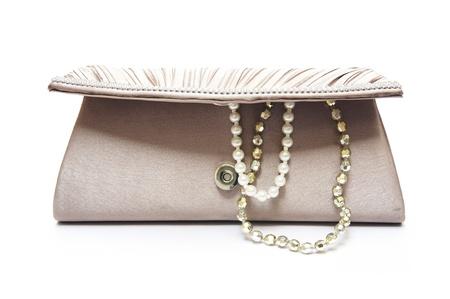 pochette marrone con gioielli su sfondo bianco