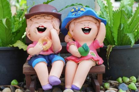 Smiling clay dolls in garden                      photo