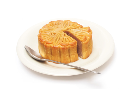 round chestnut Chinese moon cake on plate and spoon photo