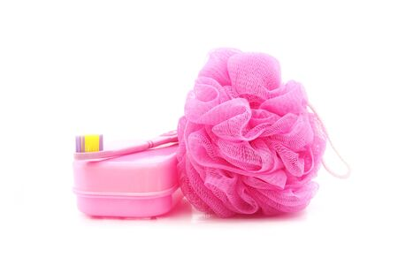 scrubber: pink toothbrush, soapboxand shower scrubber on white background