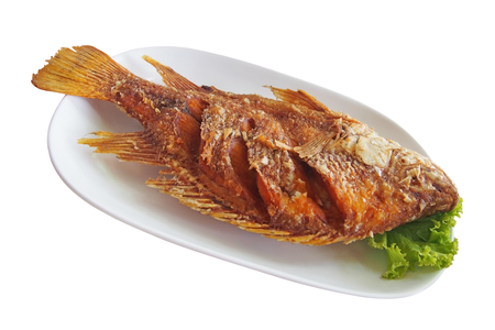 niloticus: fried nile tilapia fish with green lettuce on white plate Stock Photo