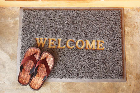 welcome mat: welcome mat with brown sandals on floor