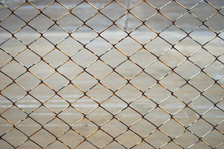 old rusty steel wire fence against blur background