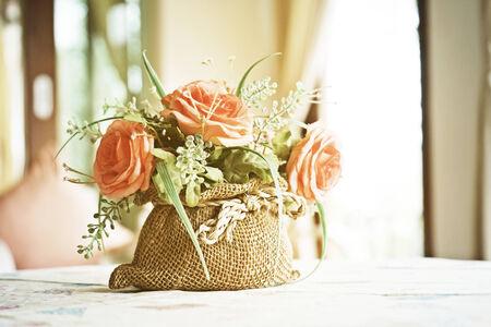 rosas naranjas: rosas artificiales de color naranja en peque�o saco en la sala de estar, estilo vintage