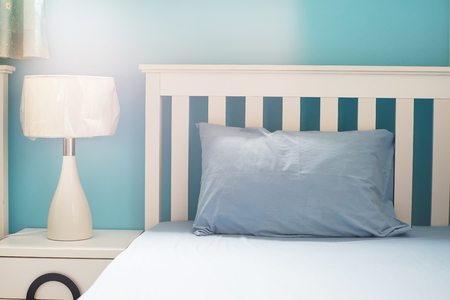 clam beds: light blue pillow on white  bed in bedroom Stock Photo