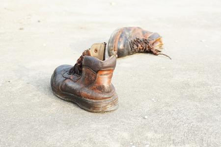 zapatos de seguridad: viejos zapatos de seguridad de cuero en el piso de concreto