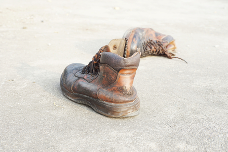 shoestring: old leather safety shoes on concrete floor