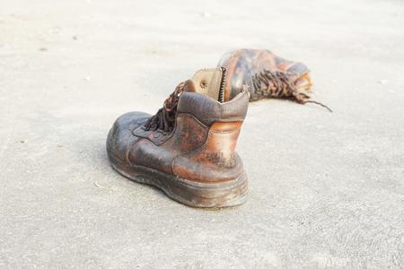 calzado de seguridad: viejos zapatos de seguridad de cuero en el piso de concreto