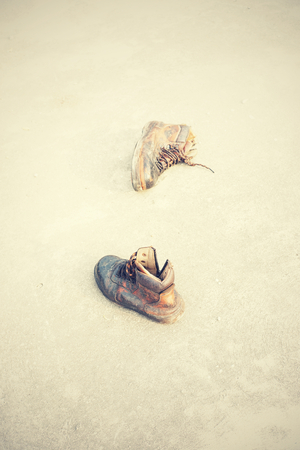 spat: old leather safety shoes on grunge concrete floor , vintage style and soft focus