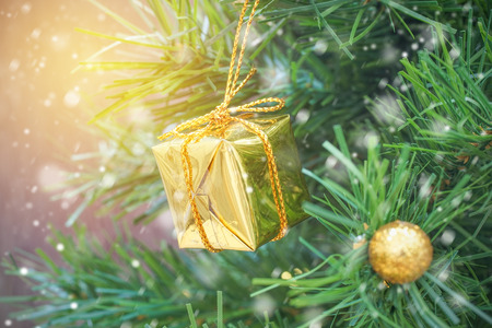 fake christmas tree: small gold gift box on christmas tree with snow falling in soft focus, holiday background Stock Photo