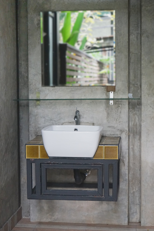 wash basin: ceramic wash basin and faucet on gray concrete wall