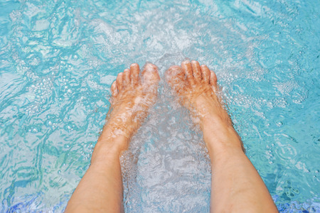 old womens feet in jacuzzi pool