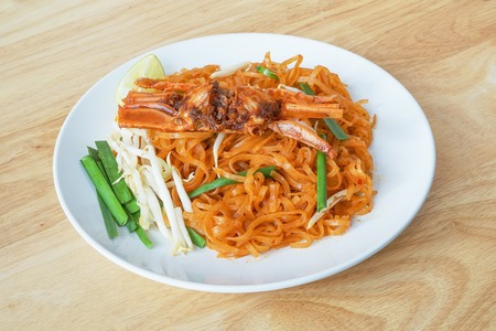 Fried rice noodles with chili sauce and crab on white plate, pad thai sen jan