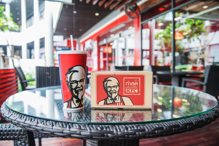 BANGKOK ,THAILAND- May 20 ,2017: KFCs cold drink and paper meal box  in front of Kentacky Fried chicken restaurant