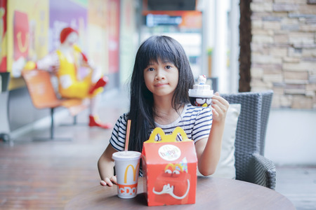 mcdonalds: BANGKOK - OCTOBER 10 : an asian girl ,in soft focus, showed her happy meal food and toy at McDonalds restaurant on October 10, 2017 in Bangkok, Thailand Editorial