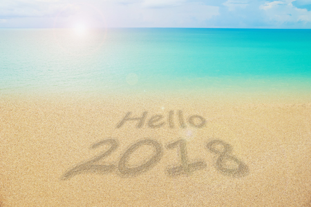 hello 2018 word on nature fine sand and calm sea with lens flare