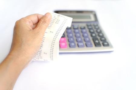 Receipt paper, selective focus, in hand with blurred calculator 版權商用圖片