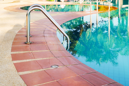 Metal handrail besides swimming pool