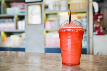 Fruit frappe in transparent plastic glass and brown straw on table with blurred bookshelf