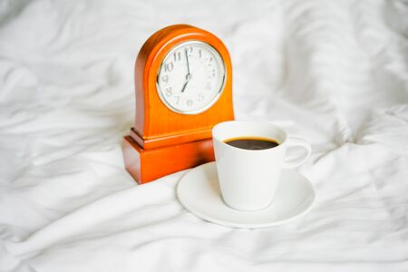 Cup of hot coffee with blurred retro clock on white bed