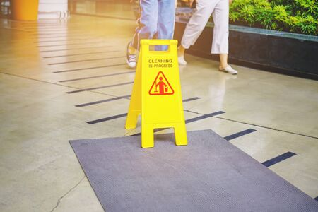 cleaning in progress sign on yellow plastic board on floor with some people walking