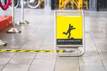 geel pas op voor ongelijke vloerbord op tegelvloer Stockfoto