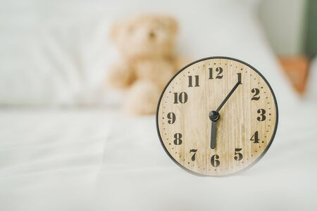analog clock on bed with blurred doll in bedroom