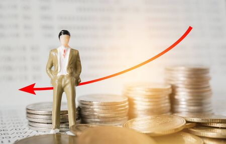 miniature business man and graph with blurred coins and bankbook , business and finance concept