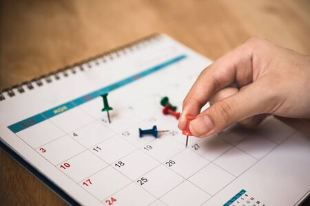 people's hand hold red push pin to mark date on calendar with vignette