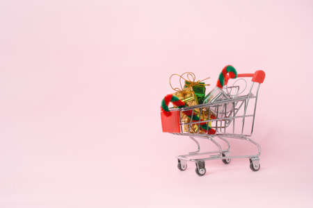candy cane and small gift boxes in shopping cart on pink background