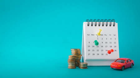 thumbtack on white calendar with miniature red car and stack of coins on grunge blue paper background with copy space , business and finance concept, car rent , loan, due date or planning to travel
