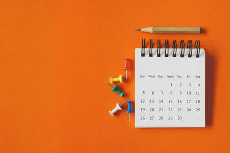 white calendar , thumbtacks and pencil on vivid grunge orange paper background , business or education concept