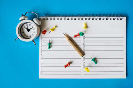 white alarm clock, opened planner, brown pencil and thumbtacks on grunge blue paper background for business or education concept