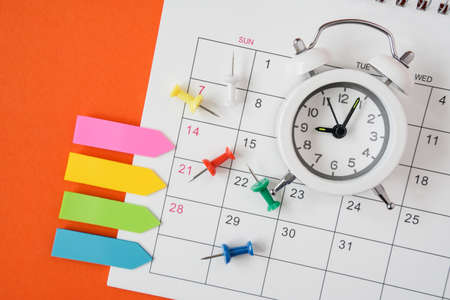 alarm clock on opened calendar with paper tag and thumbtacks with grunge orange paper background