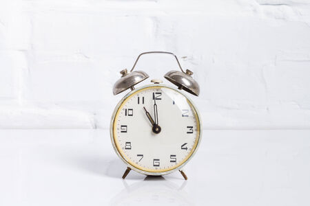 Alarm clock. Brick white wall photo