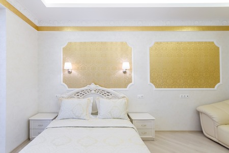 luxuriously: Luxurious bed with cushion in royal bedroom interior. Hotel room in gold tones