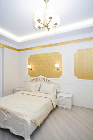 counterpane: Luxurious bed with cushion in royal bedroom interior. Hotel room in bright colors, vertical orientation pictures Stock Photo