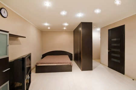 home theatre: Interior of beige living room. Spacious studio apartment with double bed and TV