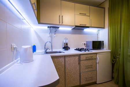 Modern small kitchen with green curtains and LED backlight Stock Photo