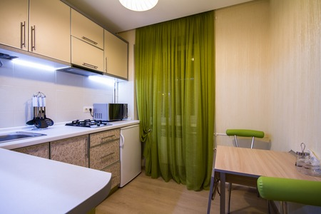 small room: Modern small kitchen with green curtains and LED backlight Stock Photo