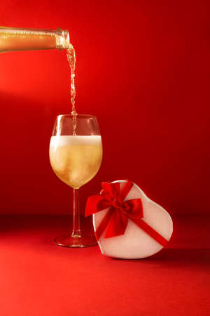 Bottle and glass of champagne and heart shaped gift box on red background. Romantic celebration greeting card of Valentines Day. Concept February 14