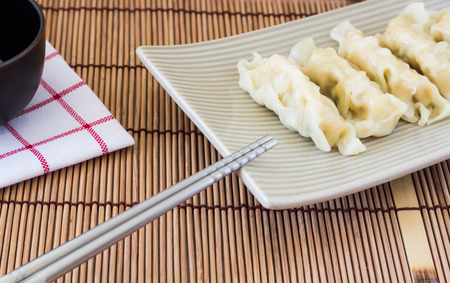 chinese meal: Picture of wonton and chopsticks on wooden background Stock Photo