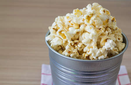 steel bucket: Picture of popcorn in steel bucket on wooden background