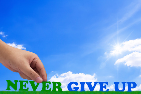 Hand holding never give up text on blue sky background, motivation and inspiration concept Stok Fotoğraf