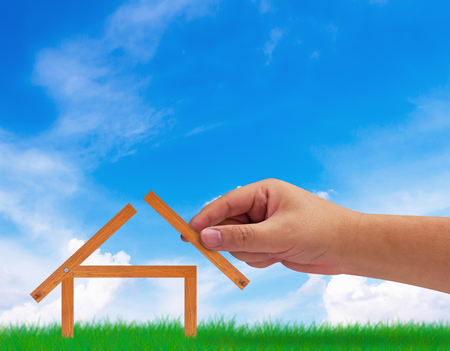 Building new house, home concept, hand holding wood plank on blue sky background