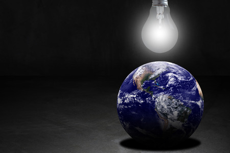 conservative: Ecology concept, save energy, the earth and light bulb on dark background, Elements of this image furnished by NASA Stock Photo